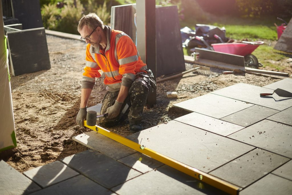 How to Lay Porcelain Slabs - man laying slabs